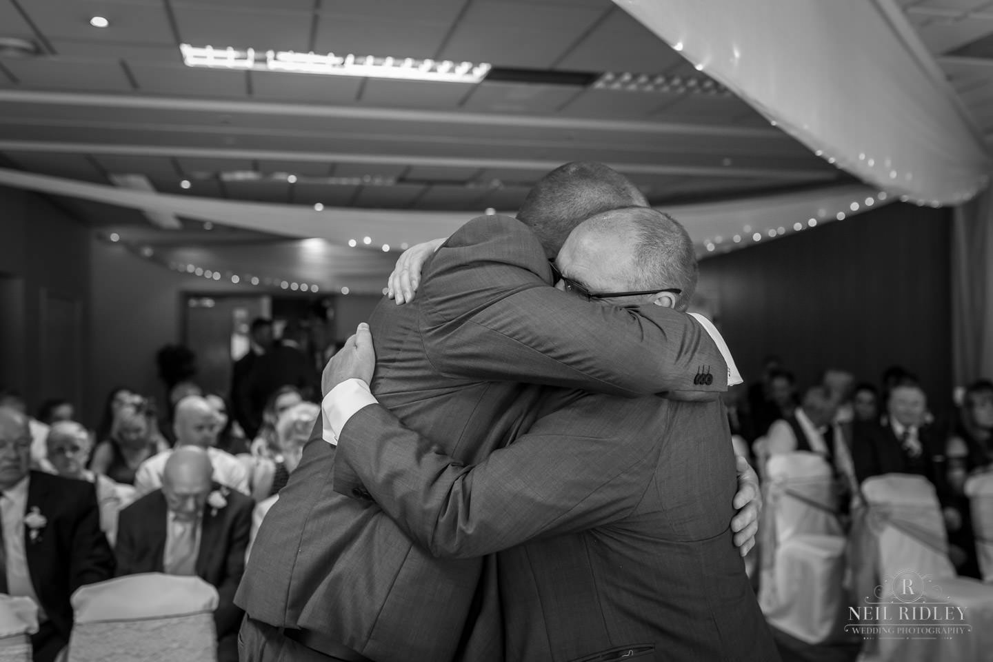 Groom and his best man embrace at the altar at Macdonald Portal Hotel, Tarporley