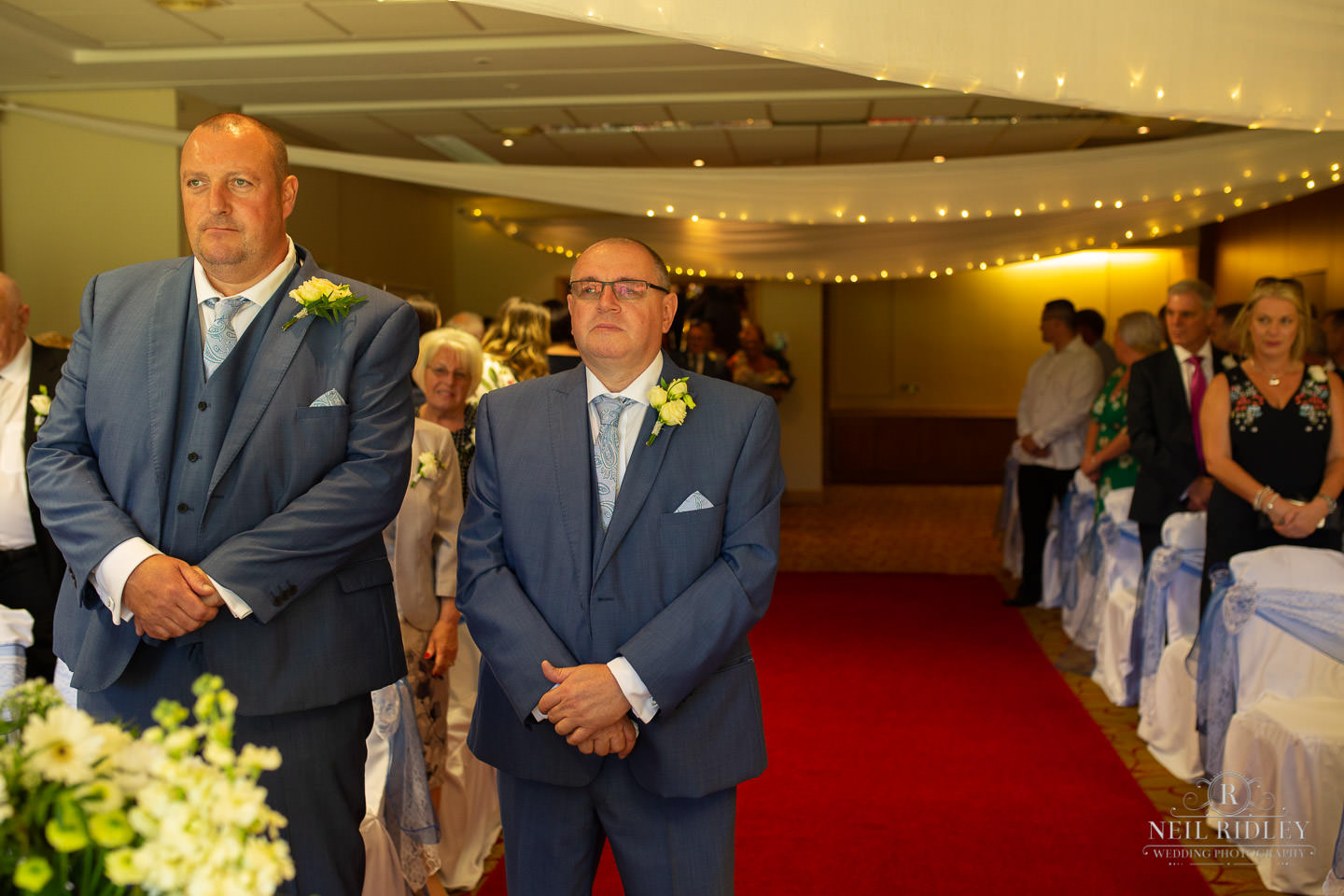 Groom stands at the altar with best man at Macdonald Portal Hotel, Tarporley
