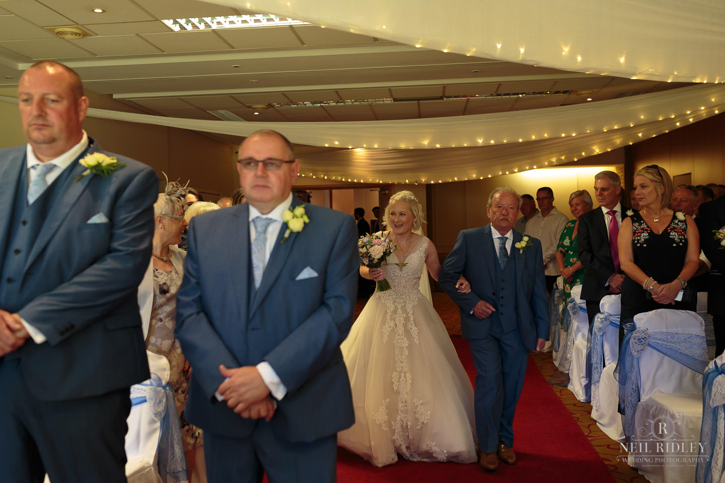 Bride walks down the aisle on her fathers arm whilst the grrom waits at Macdonald Portal Hotel, Tarporley
