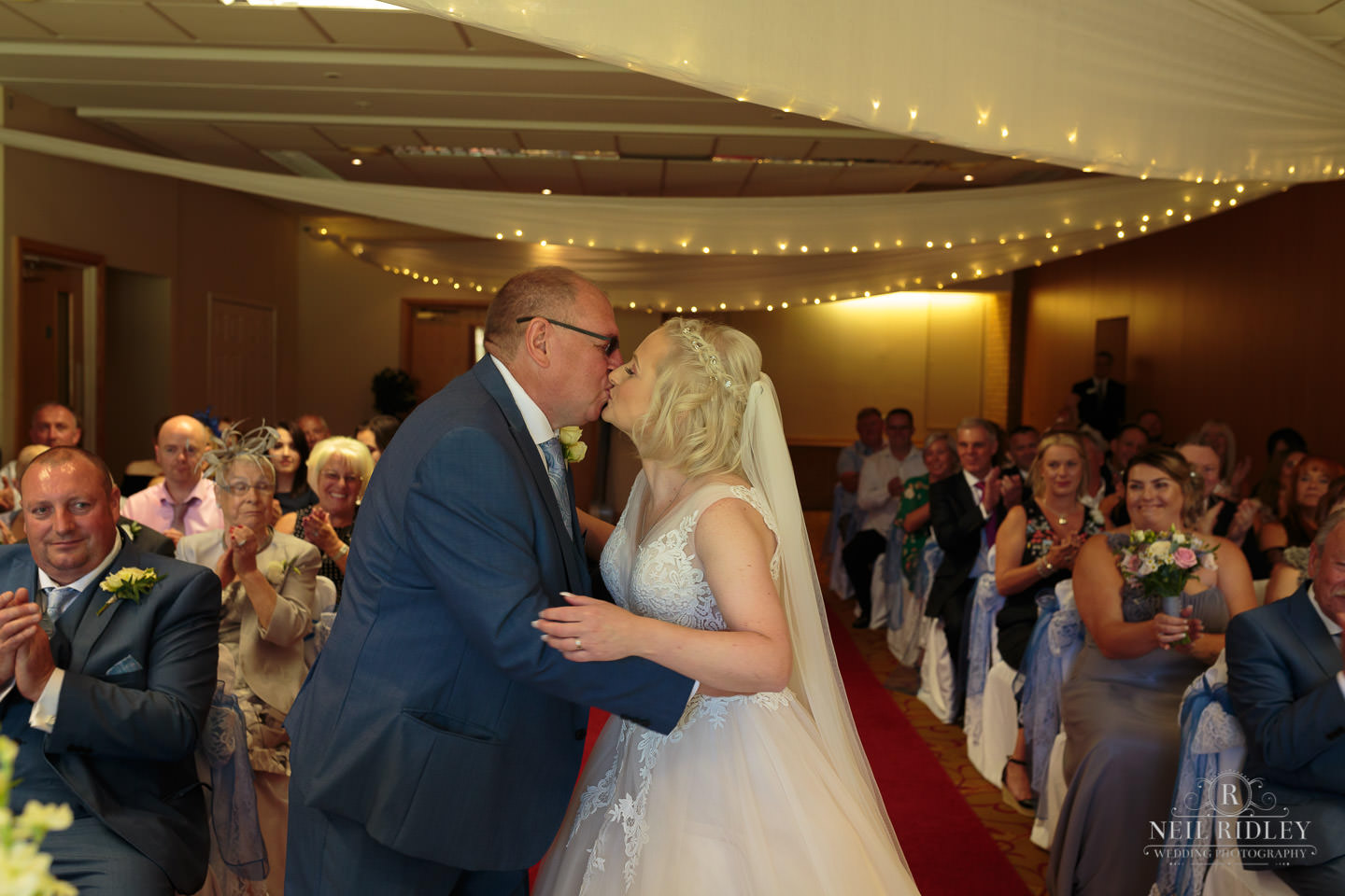 Bride and Groom kiss at the altar at Macdonald Portal Hotel, Tarporley
