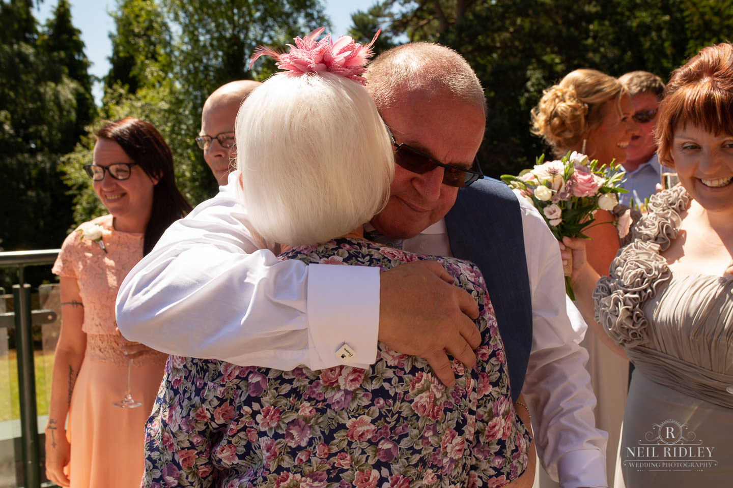 Groom hugs his mother in law outside at Macdonald Portal Hotel, Tarporley