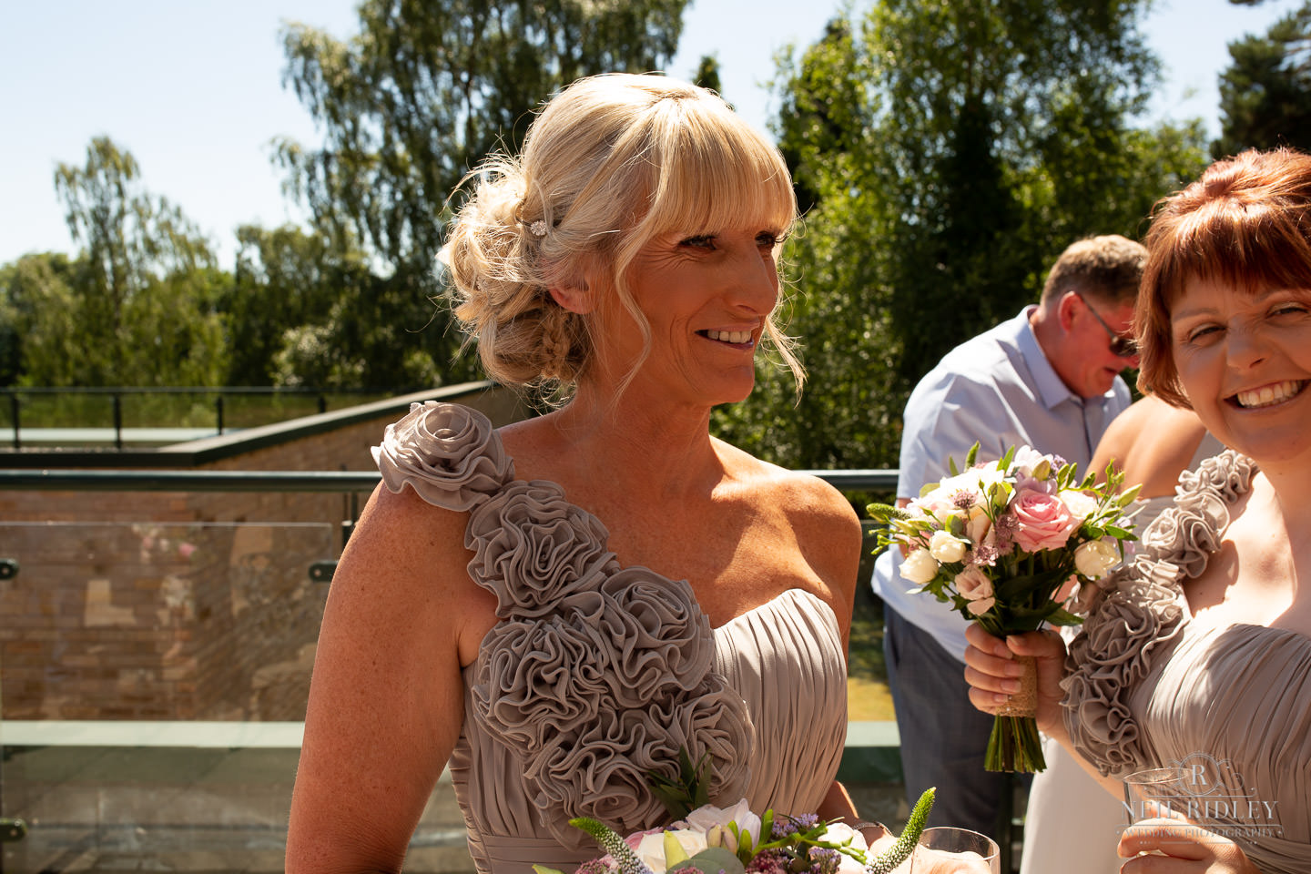Bridesmaid standfs outside in the sunshine at Macdonald Portal Hotel, Tarporley
