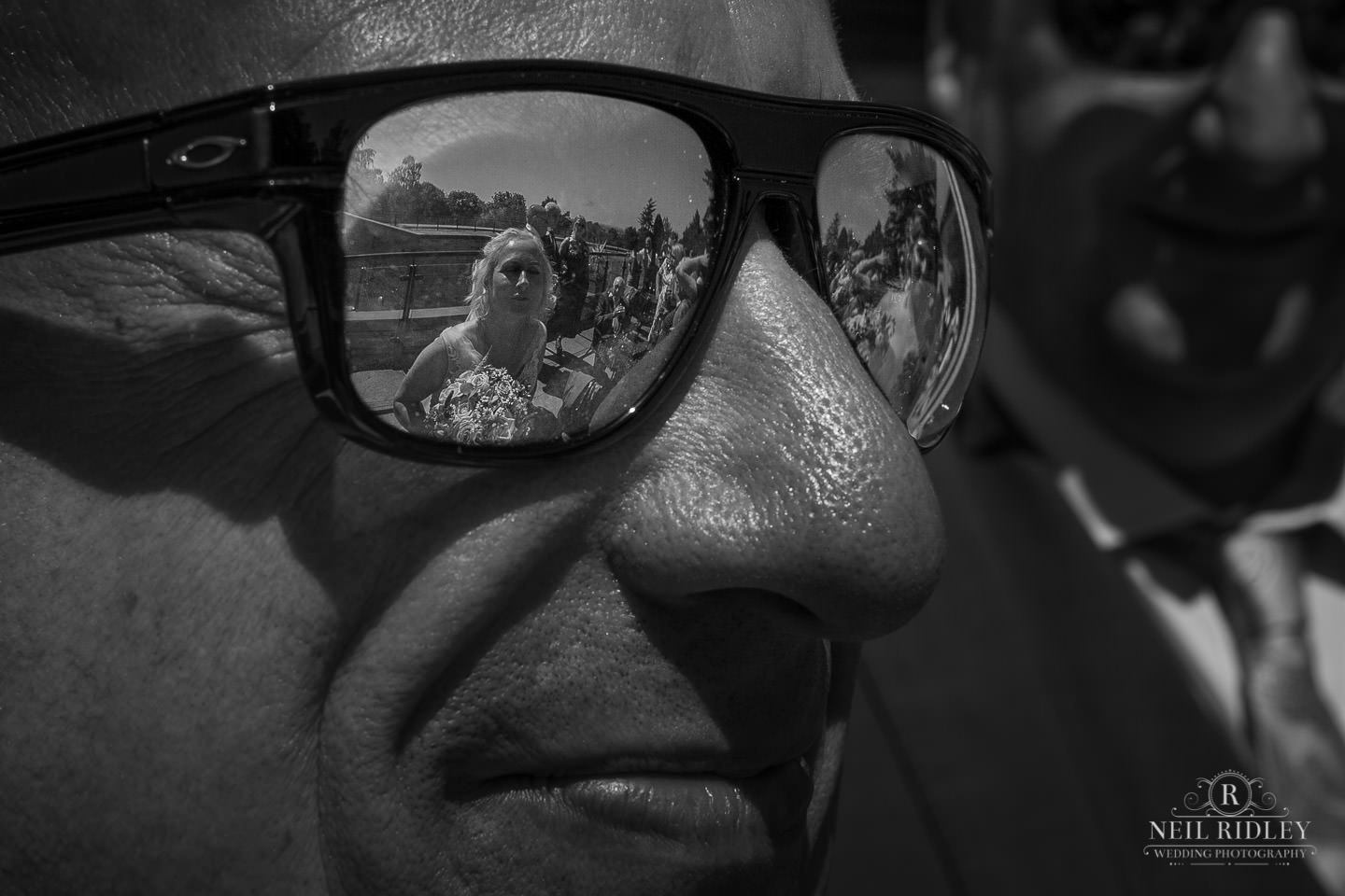 Black and white image of wedding guest wearing sunglasses with Brides reflection in the lens at Macdonald Portal Hotel, Tarporley