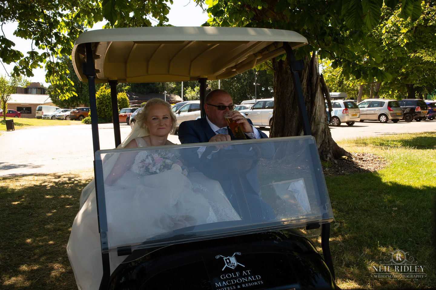 Bride and Groom in golf buggy at Macdonald Portal Hotel, Tarporley