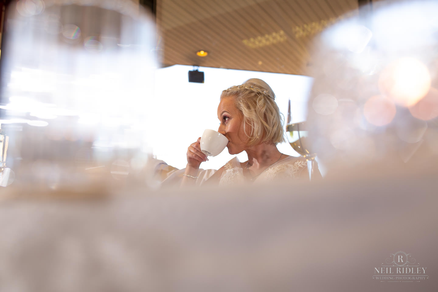 Bride drinks a cup of tea during her wedding breakfast at Maccdonald Portal Spa and Hotel