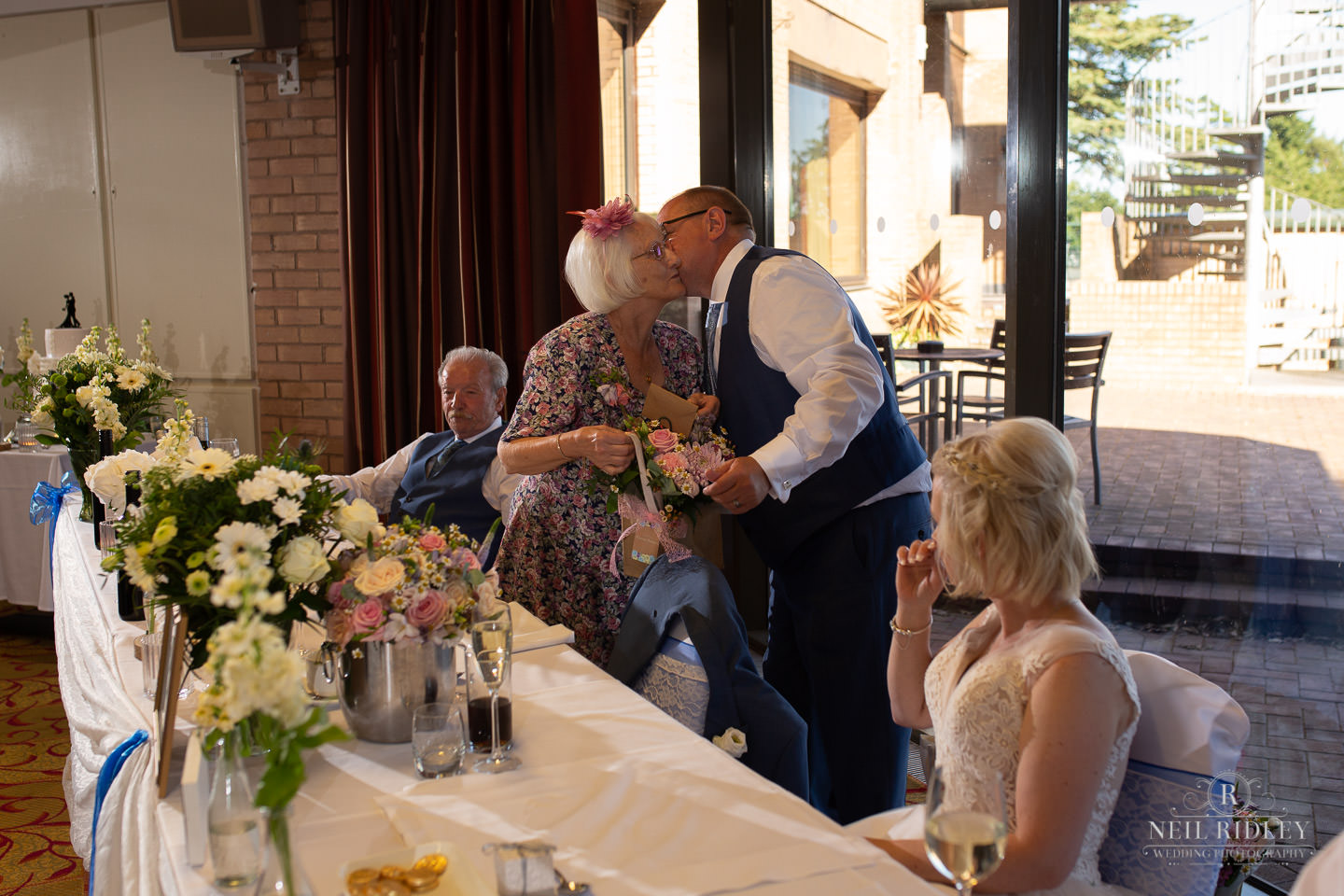 Groom gives a bouquet of flowers to mother of the bride during the Wedding breakfast at Maccdonald Portal Spa and Hotel