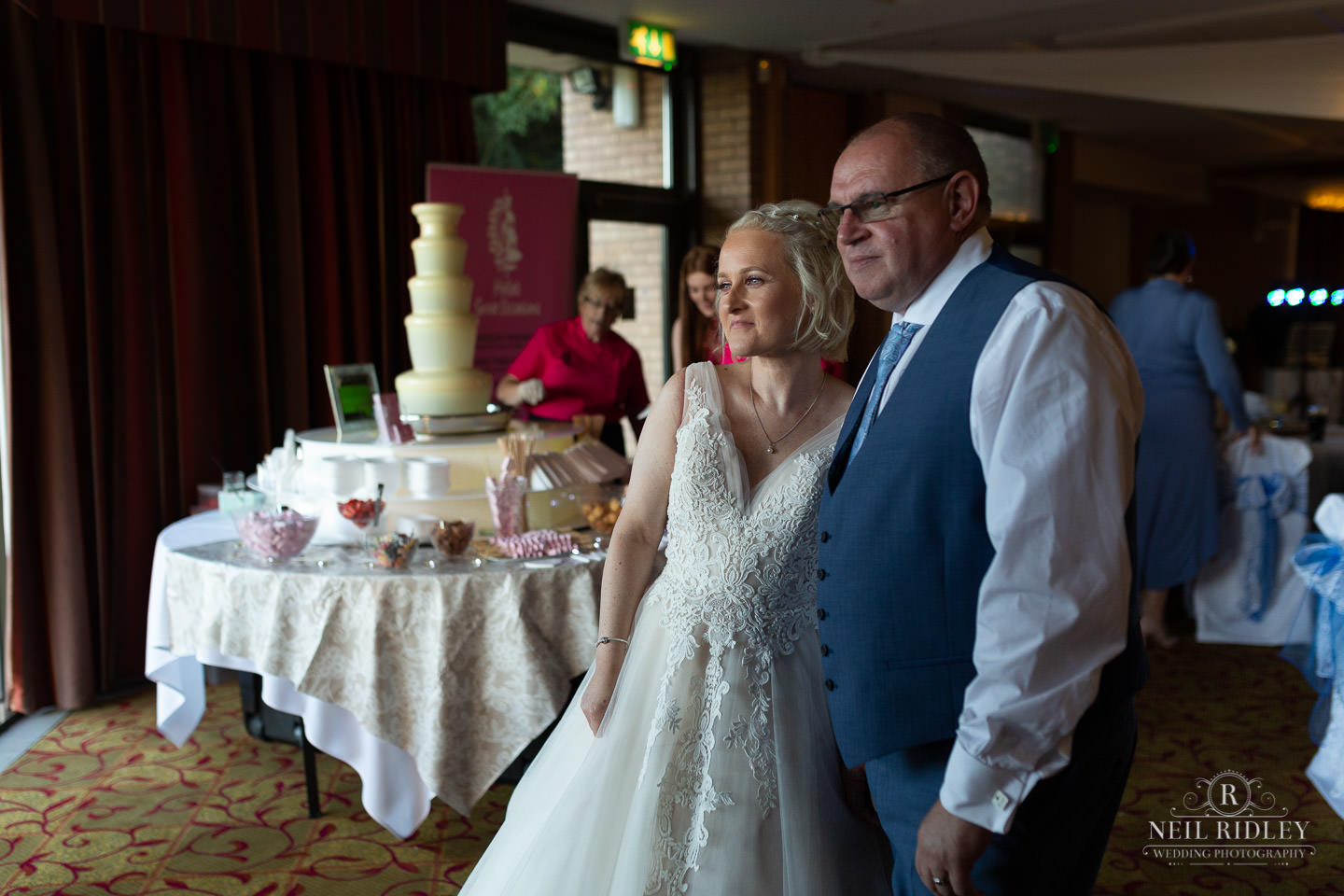 bride and groom stand in front of chocolate fountain at Maccdonald Portal Spa and Hotel