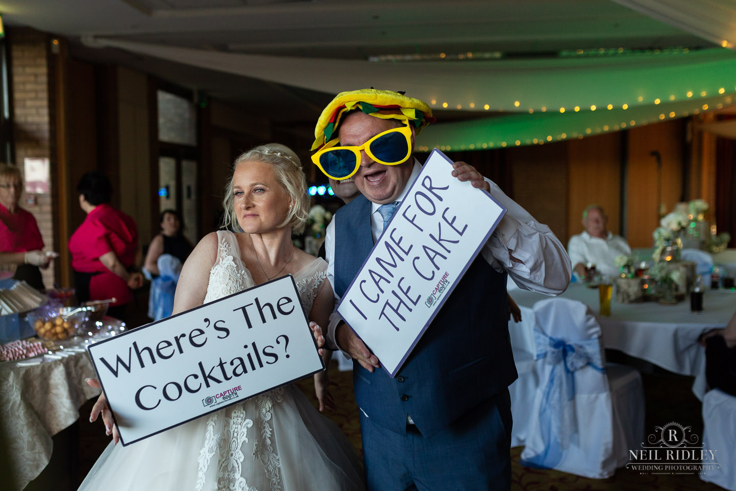 Bride and groom stand in front of magic mirror with funny hats and sunglasses at Maccdonald Portal Spa and Hotel