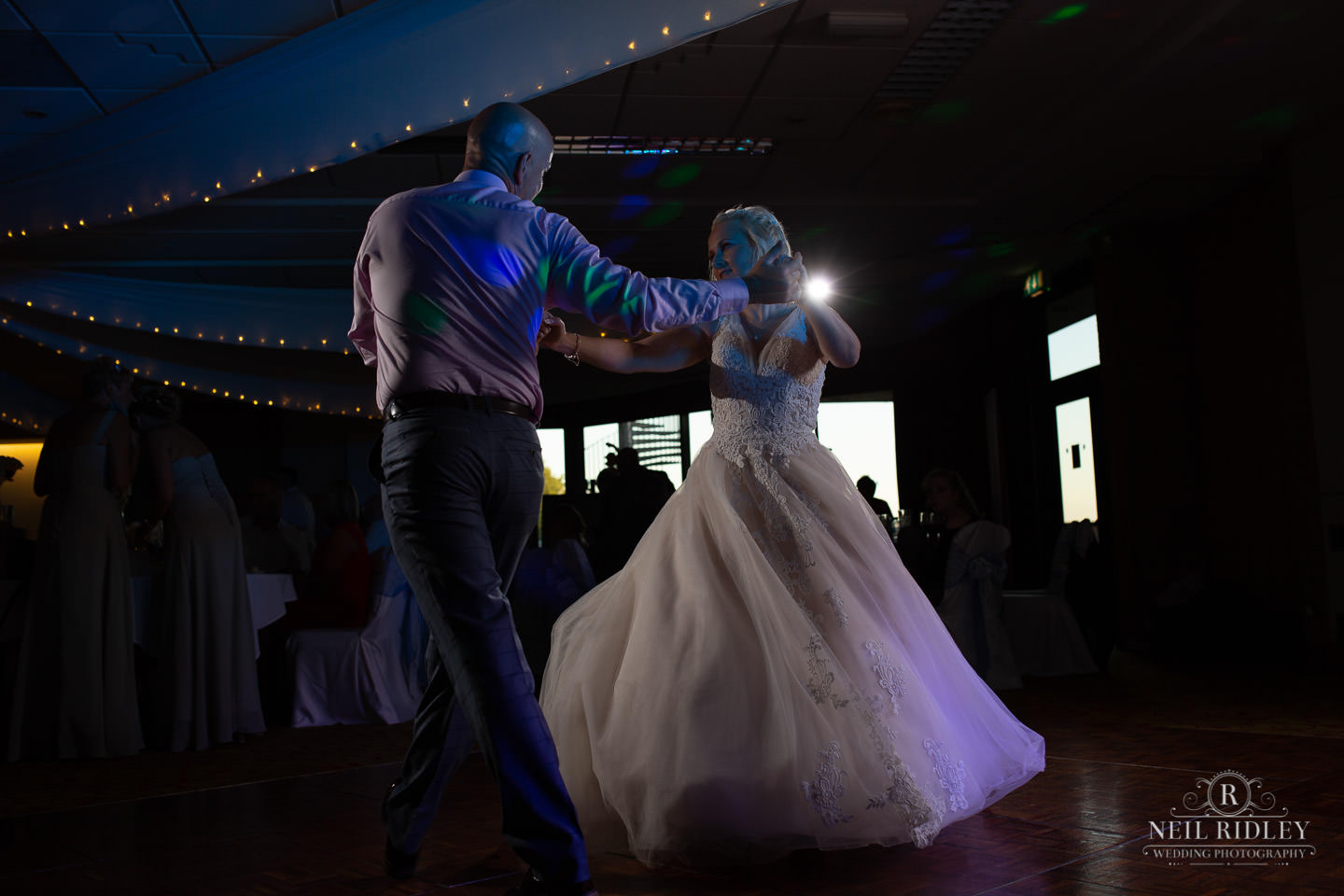 Bride and wedding guest do the tango on the dance floor at Macdonal Portal Hotel, Tarporley