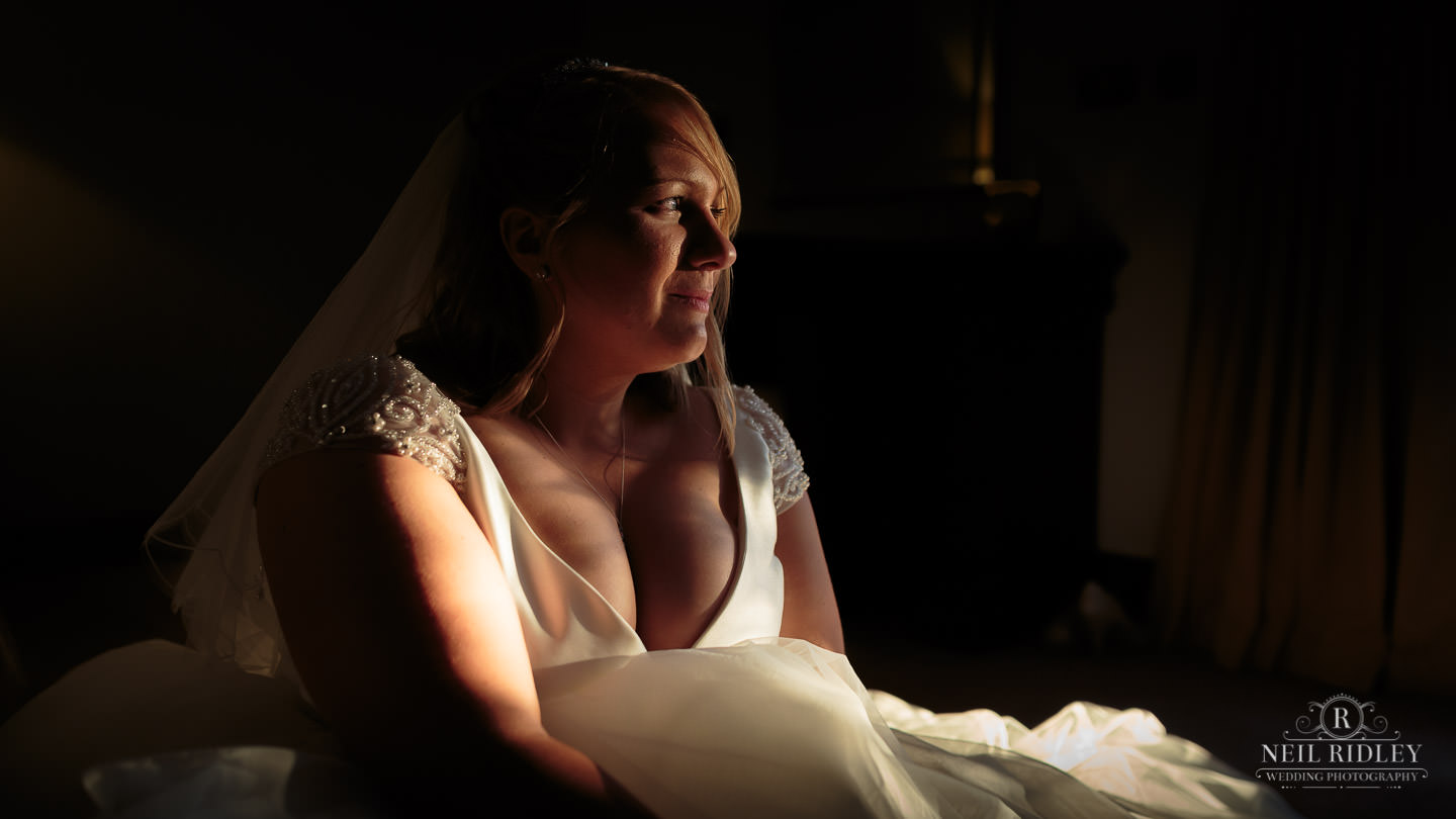 Bride in her wedding dress looking to the side with natural sunlight on her face
