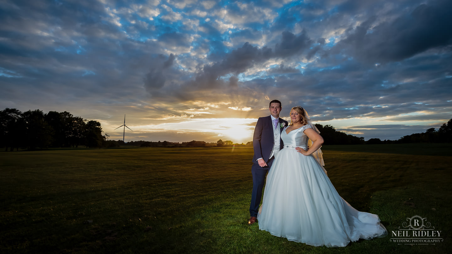 Bride and Groom stand in the grounds of Garstang Country Hotel and Golf club with sun setting behind them