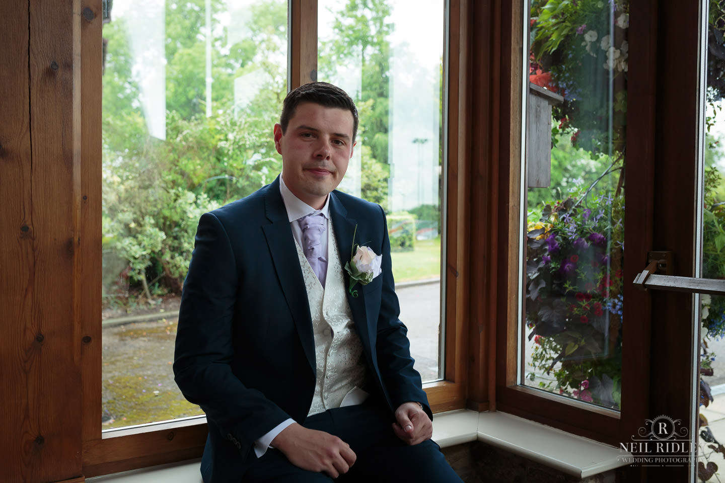 Groom sits in the entrance at Garstang Country House Hotel and Golf Club