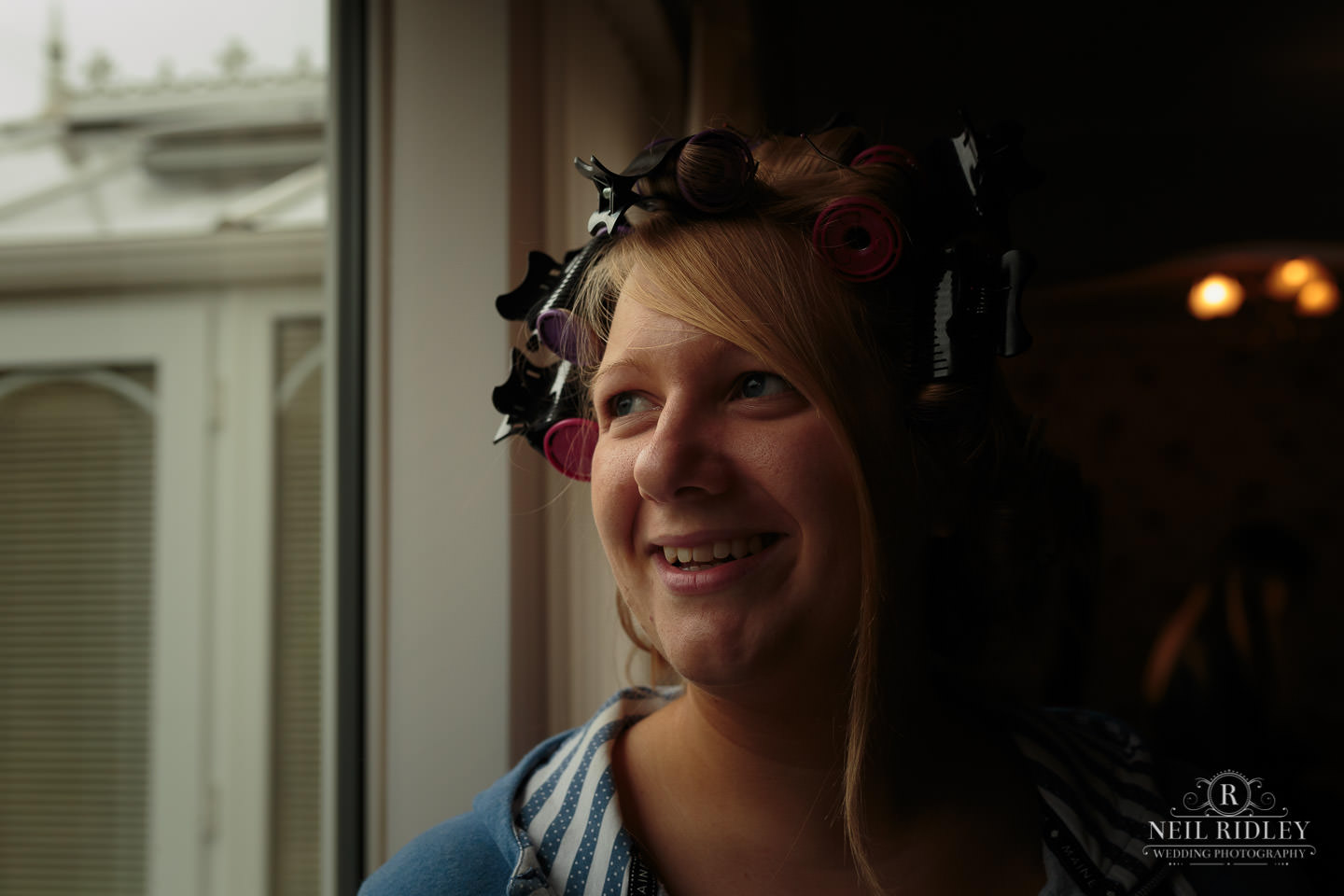 Bride with Curlers in her hair looking out of window during Bridal Prep