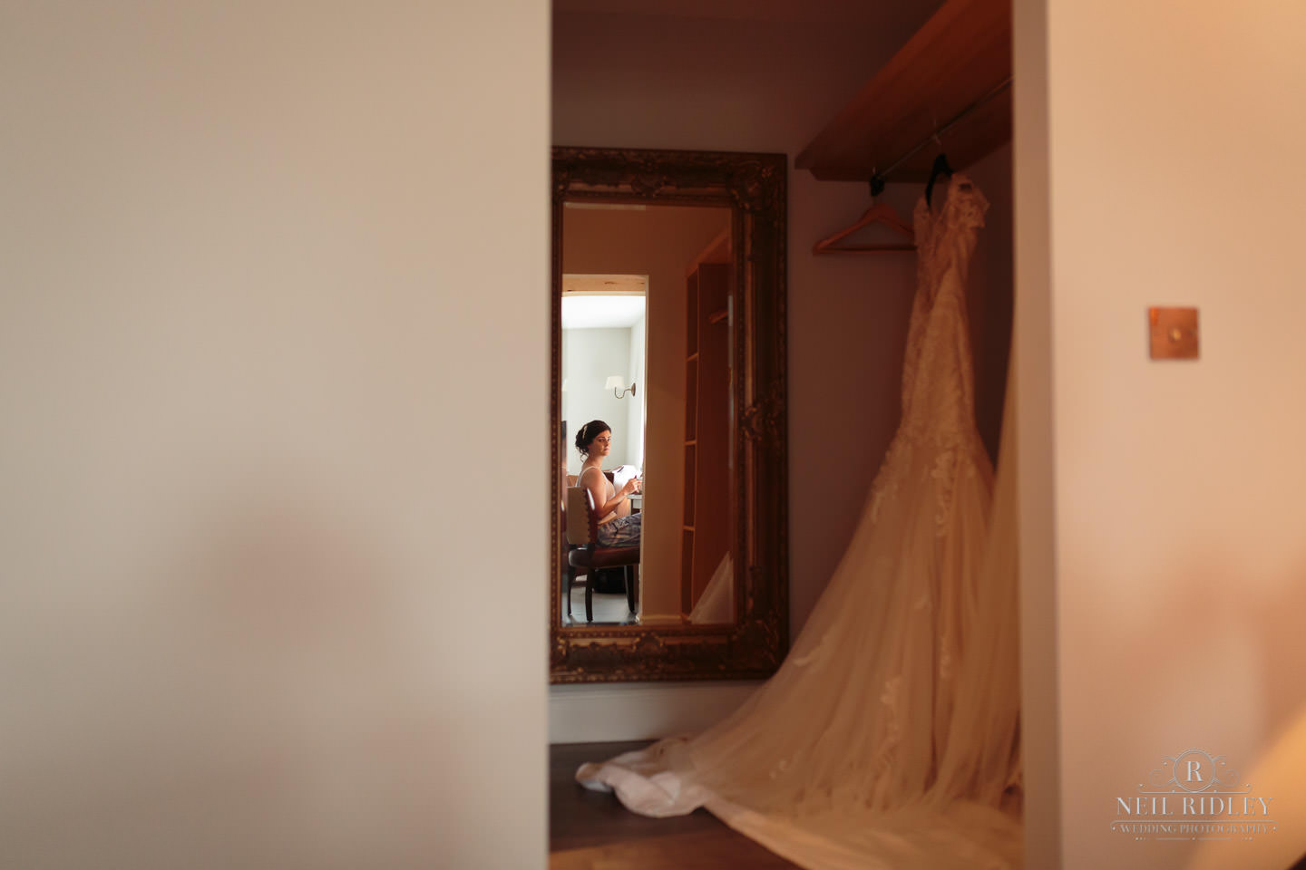 Bride sits doing make up with her reflection in the mirror with her dress hanging up at The Mill at Conder Green
