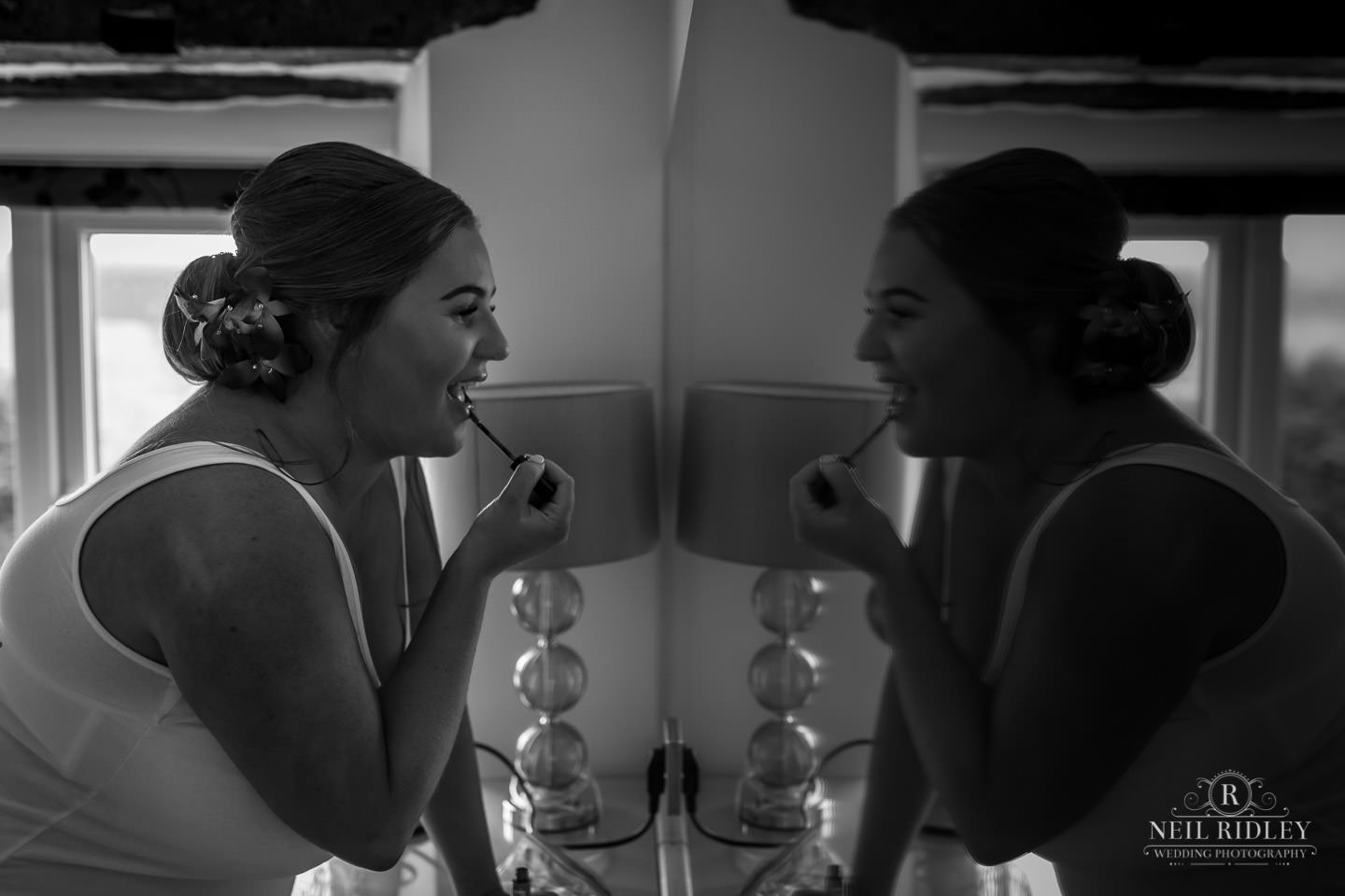 Black and white image of bridesmaid applying her lipstick with her reflection in the mirror during Bridal Prep at The Mill at Conder Green