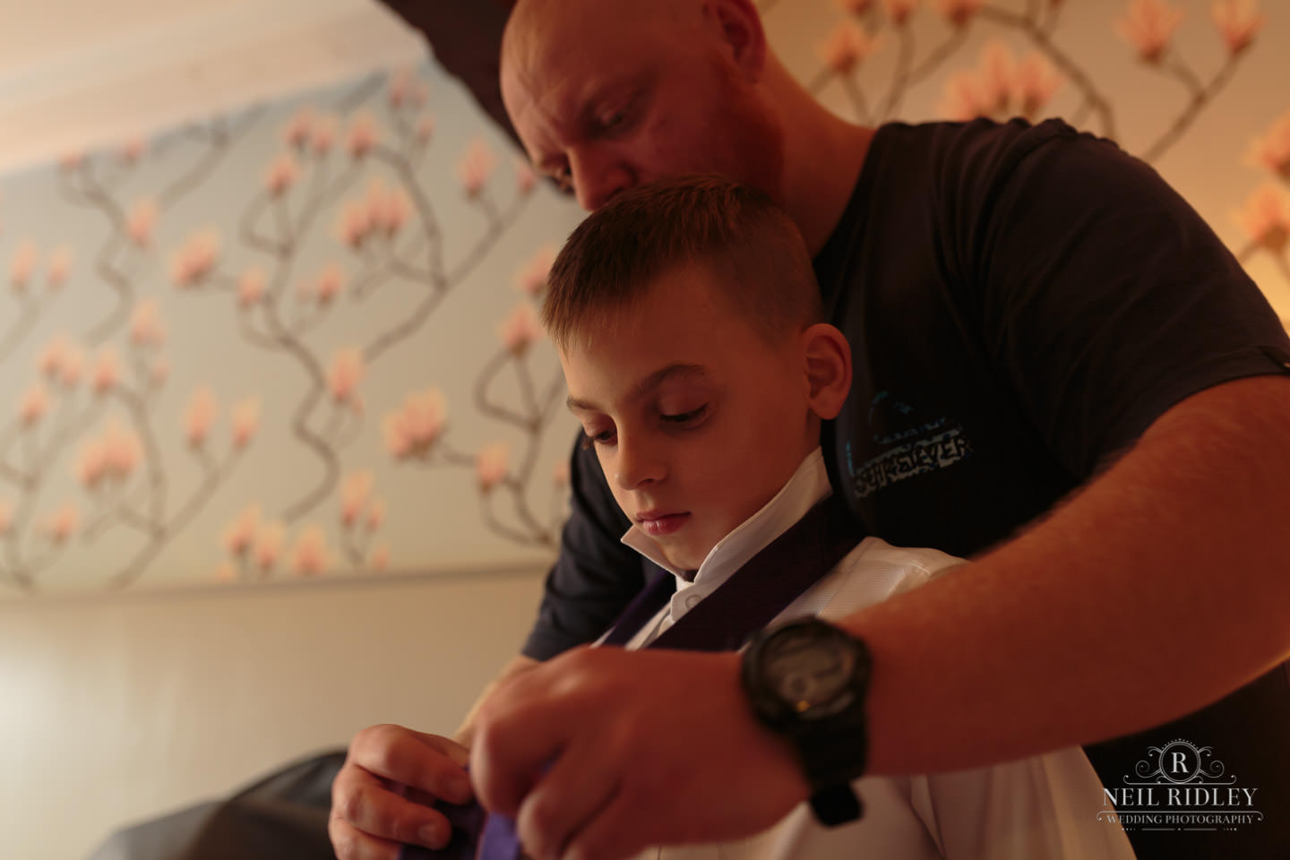 Best man tying the Page Boy's tie during Groom Prep at The Mill at Conder Green