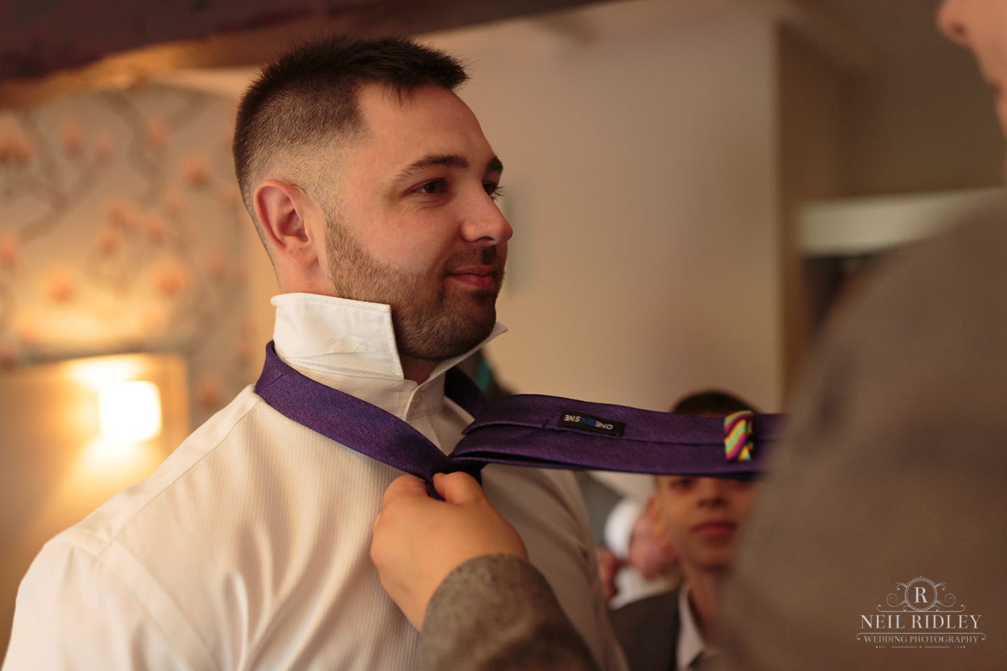 Groom having his tie tied during Groom Prep at The Mill at Conder Green