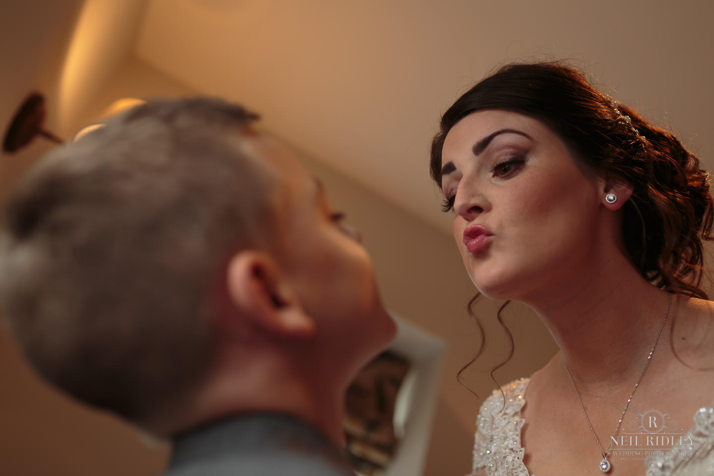 Bride kisses young son during bridal prep at The Mill at Conder Green