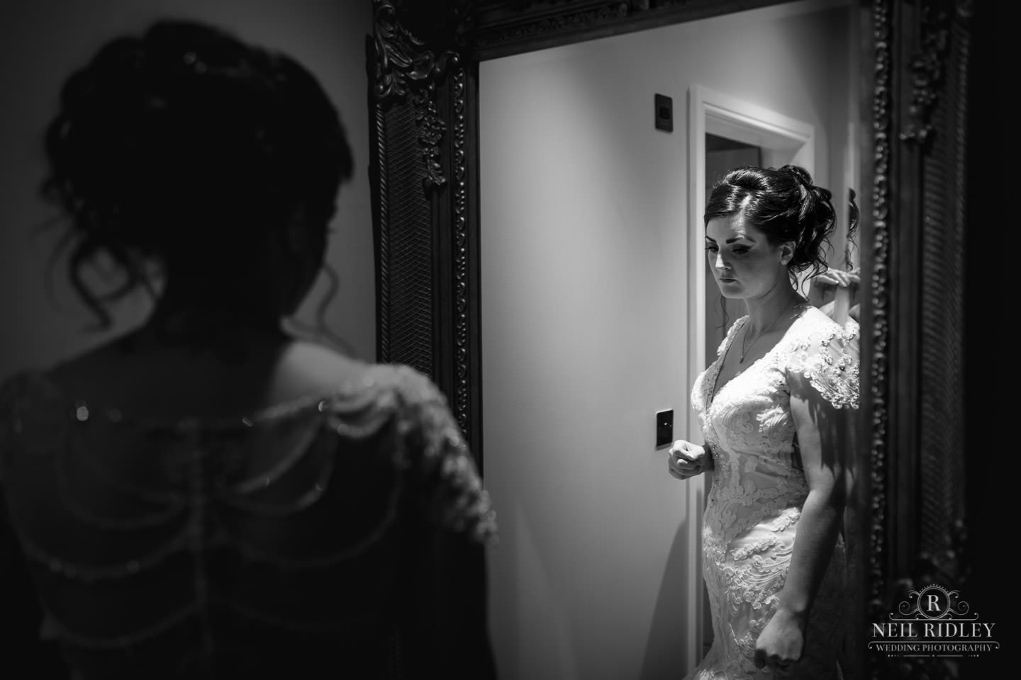 Black and white image of bride looking in the mirror with her reflection captured during Bridal Prep at The Mill at Conder Green