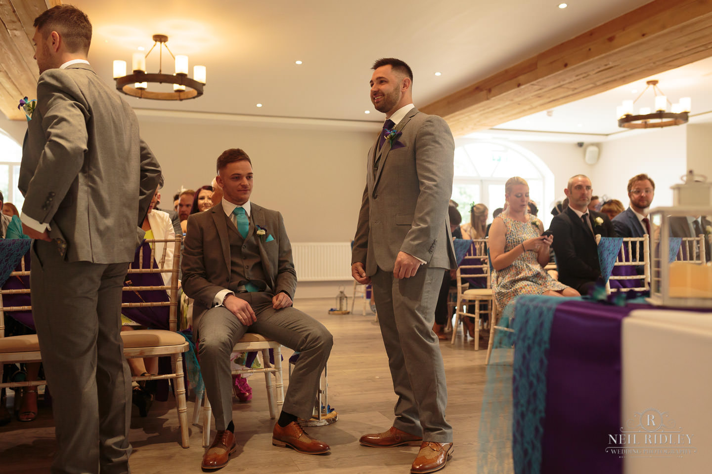 Groom stand waiting for his bride with his ushers seated at The Mill at Conder Green