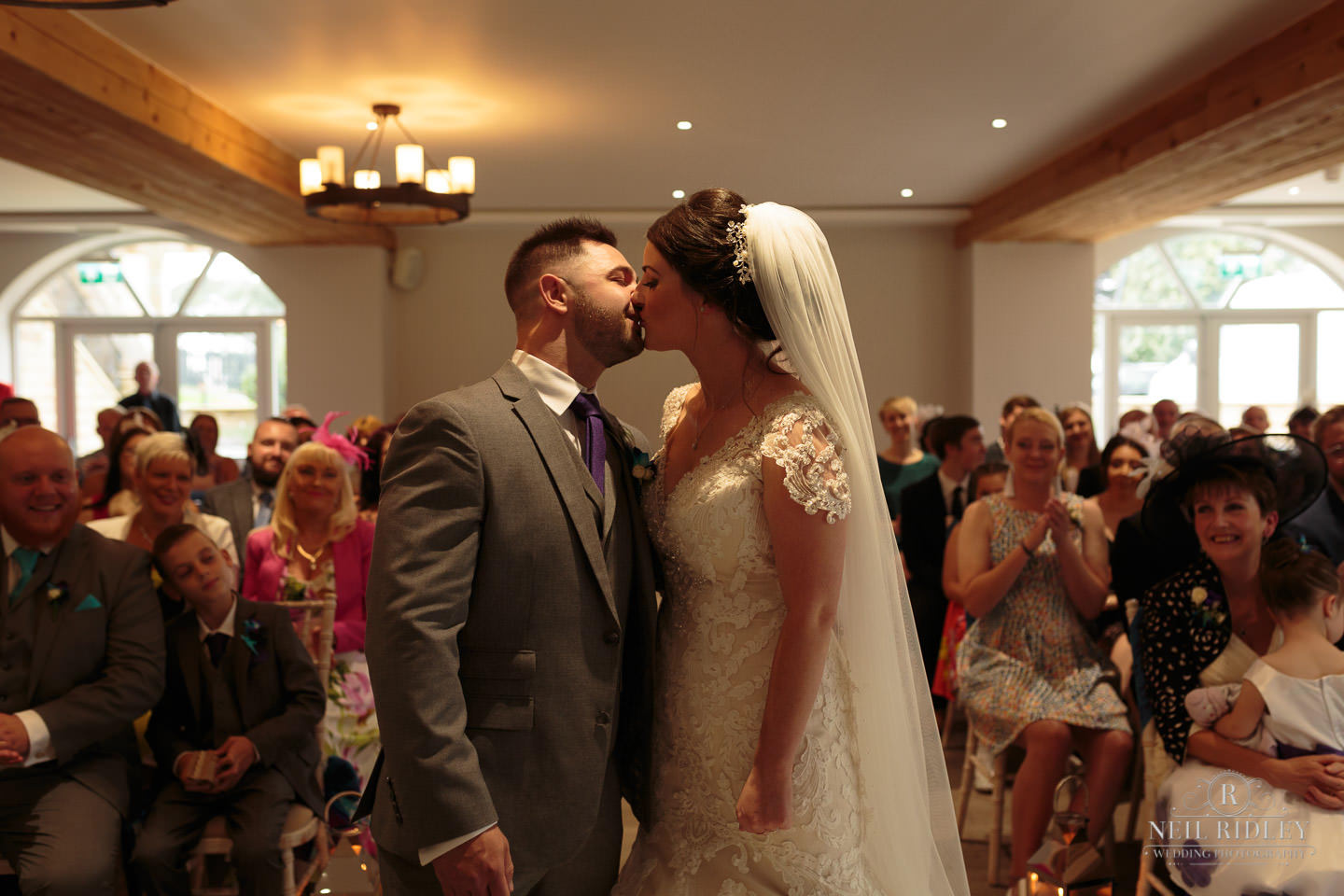 Bride and Groom exchange a kiss at the altar at The Mill at Conder Green