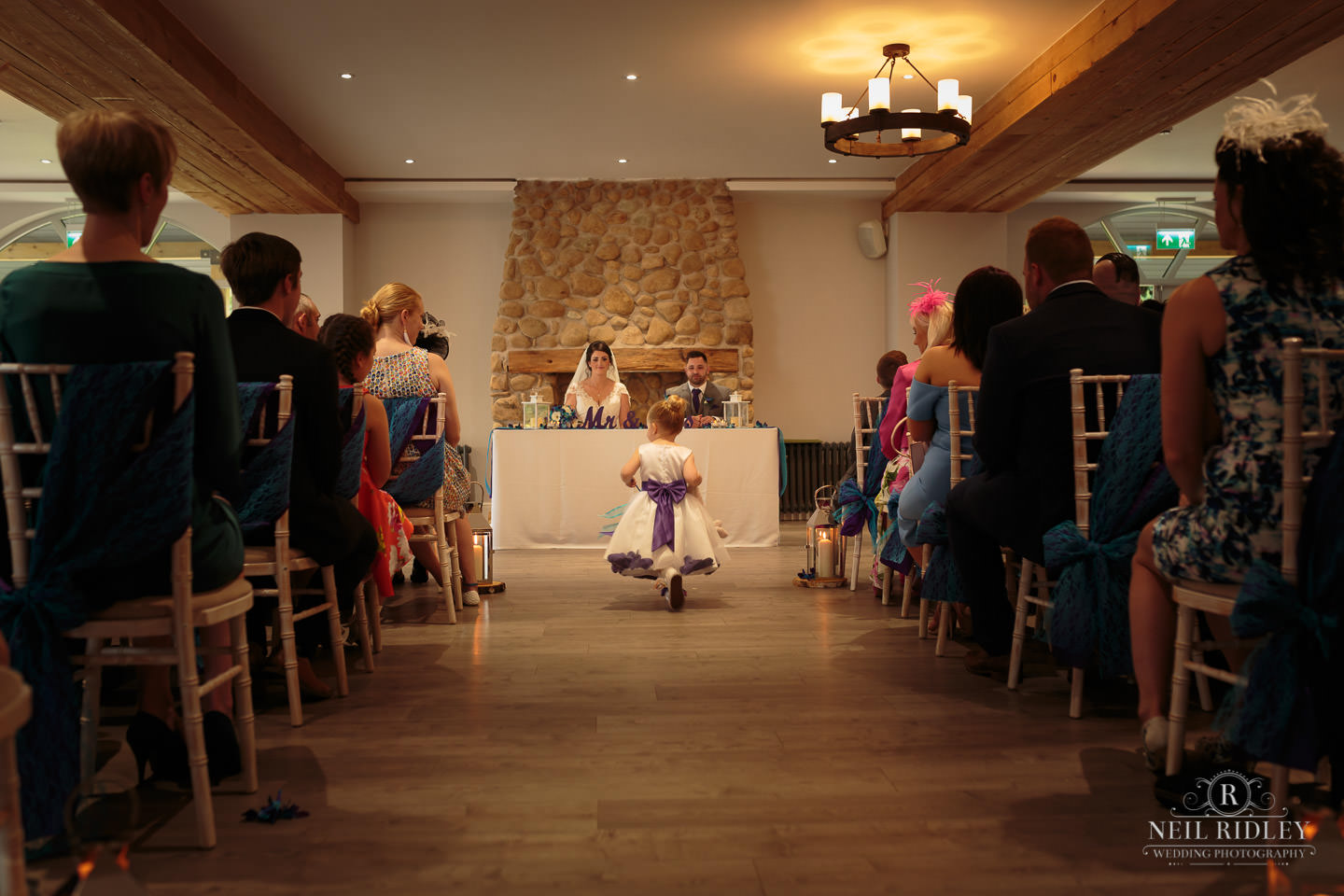 Little girl walks down the aisle during the wedding ceremony at The Mill at Conder Green