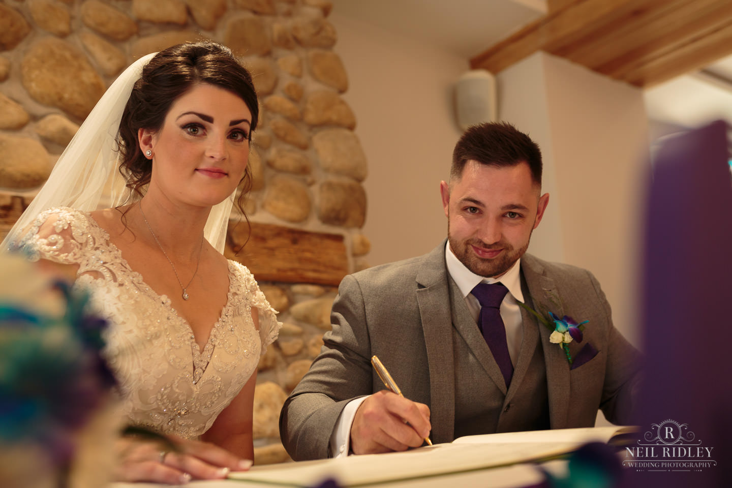 Bride and Groom sign the wedding registrar at The Mill at Conder Green