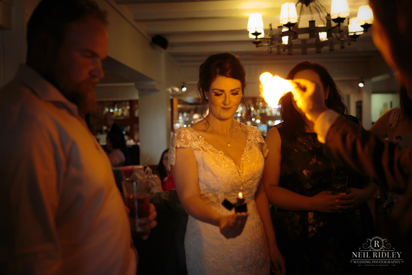 Bride watches magician burn a playing card at The Mill at Conder Green