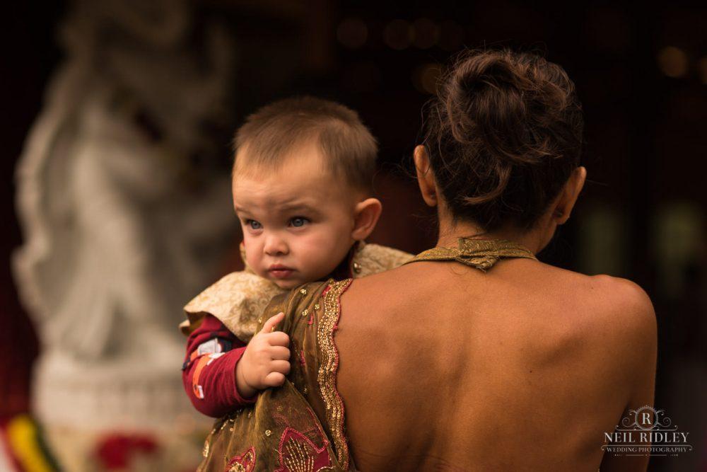 Merrydale Manor Wedding Photographer - Baby looks over mothers shoulder