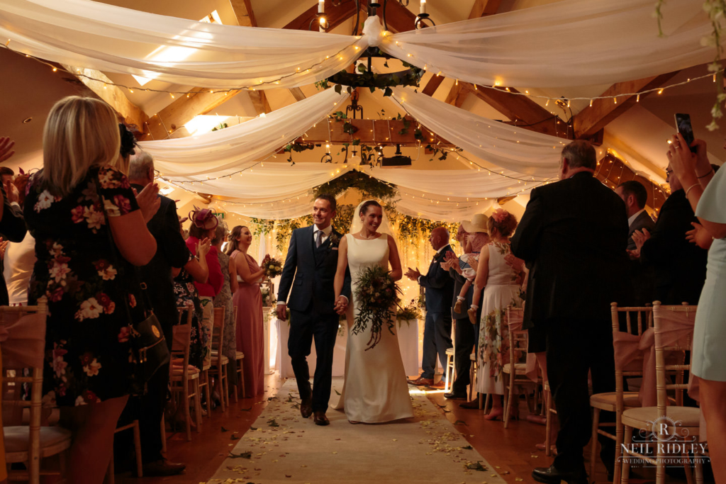 Beeston Manor Wedding Photographer - Bride and Groom walk down the aisle